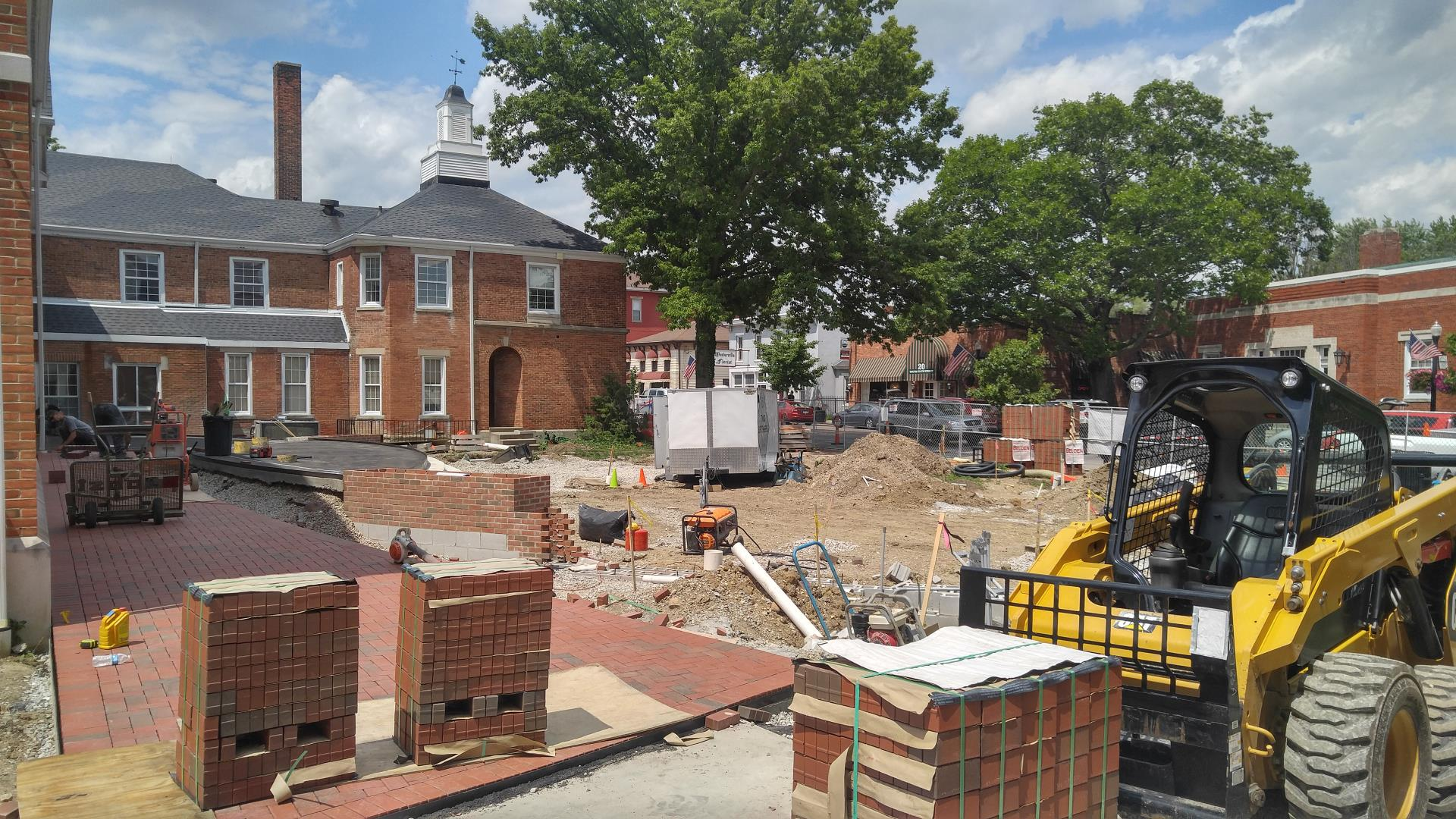 Crews lay bricks along the newly-poured pathway to City Hall.